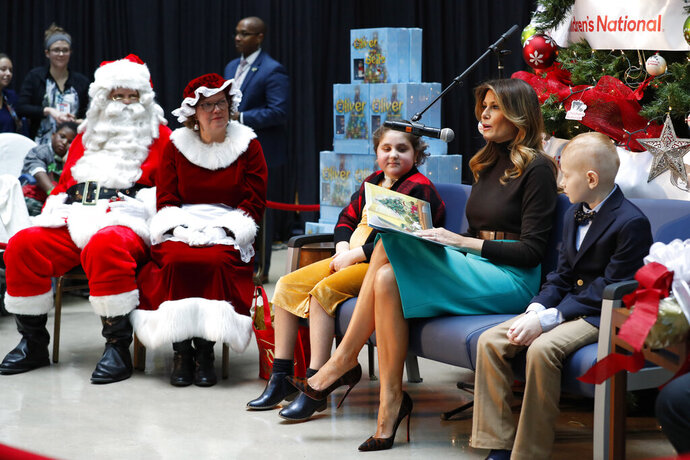 First lady Melania Trump reads a Christmas book to children as she is seated between patients at Children's National Hospital, Sammie Burley, left, and Declan McCahan, right, Friday, Dec. 6, 2019, in Washington. (AP Photo/Jacquelyn Martin)