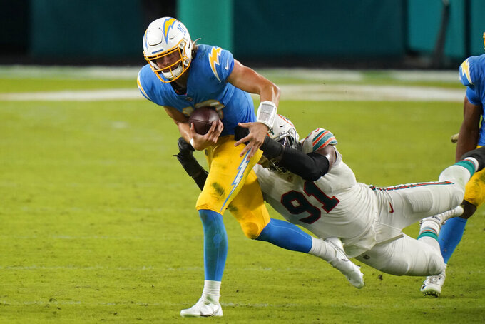 Miami Dolphins defensive end Emmanuel Ogbah (91) sacks Los Angeles Chargers quarterback Justin Herbert (10) during the first half of an NFL football game, Sunday, Nov. 15, 2020, in Miami Gardens, Fla. (AP Photo/Wilfredo Lee)