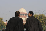 Supreme Court Lawyers speak to each other on the lawns of India's Supreme Court as it begins hearing dozens of petitions that seek revocation of a new citizenship law amendment in New Delhi, India, Wednesday, Jan. 22, 2020. The new law had led to nationwide demonstrations and a violent security backlash resulting in the death of more than 20 people. (AP Photo/Altaf Qadri)