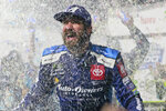 Martin Truex Jr. is doused with water and confetti after winning a NASCAR Cup Series race at Martinsville Speedway in Martinsville, Va., Sunday, Oct. 27, 2019. (AP Photo/Steve Helber)