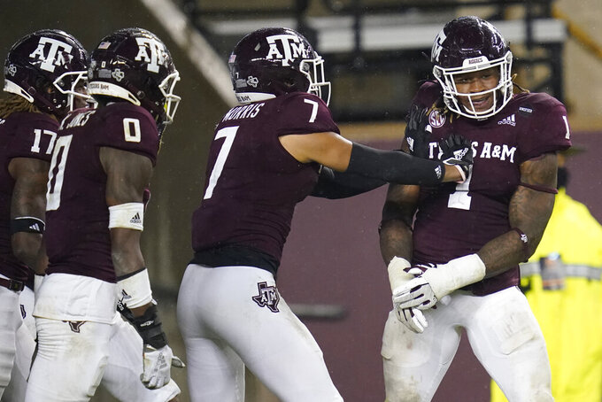 Texas A&M linebacker Buddy Johnson (1) reacts with teammates after he intercepted a pass from LSU and returned it for a touchdown during the third quarter of an NCAA college football game, Saturday, Nov. 28, 2020, in College Station, Texas. (AP Photo/Sam Craft)