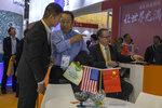 In this photo taken Wednesday, Nov. 6, 2019, visitors chat near American and Chinese flags displayed at a booth of an American company promoting environmental sensors during the China International Import Expo in Shanghai. Washington and Beijing have agreed to cancel tariff hikes as their trade negotiations progress, a Chinese Commerce Ministry spokesman said Thursday, Nov. 7, 2019. (AP Photo/Ng Han Guan)