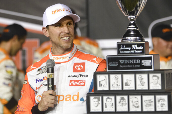 Denny Hamlin looks at the trophy after winning a NASCAR Cup Series auto race Sunday, Sept. 5, 2021, in Darlington, S.C. (AP Photo/John Amis)