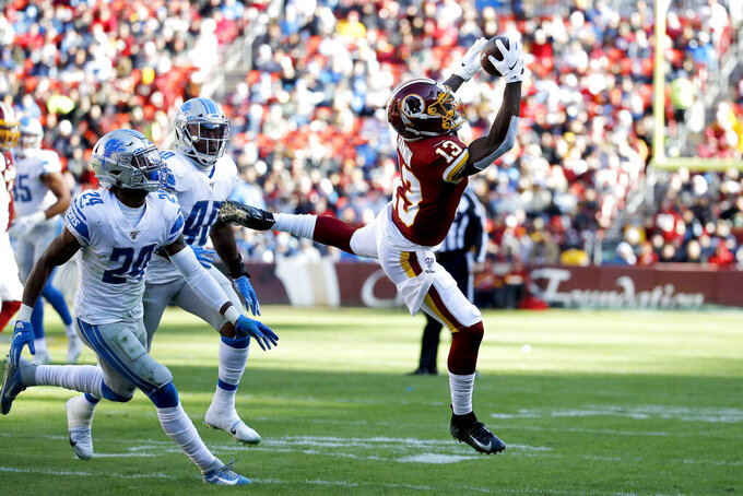 Washington Redskins wide receiver Kelvin Harmon (13) makes a catch on a pass from quarterback Dwayne Haskins, not visible, as Detroit Lions cornerback Amani Oruwariye (24) and middle linebacker Jarrad Davis (40) defend during the first half of an NFL football game, Sunday, Nov. 24, 2019, in Landover, Md. (AP Photo/Patrick Semansky)
