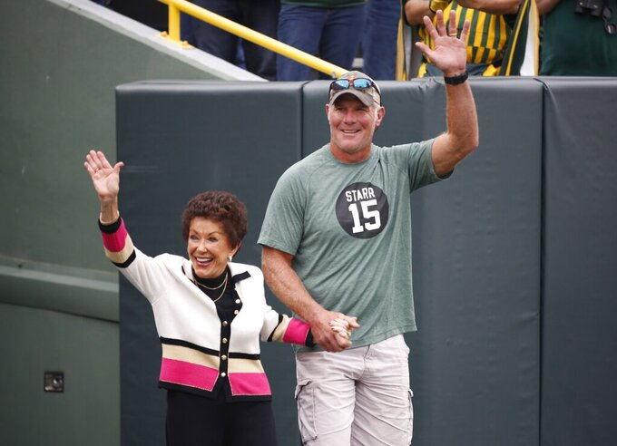Former Green Bay Packers quarterback Brett Favre escorts Sherry Starr out of the tunnel before an NFL football game between the Green Bay Packers and the Minnesota Vikings Sunday, Sept. 15, 2019, in Green Bay, Wis. (AP Photo/Matt Ludtke)