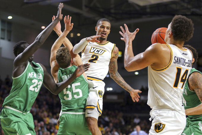 Virginia Commonwealth's Marcus Evans (2) passes the ball to Marcus Santos-Silva (14) during the first half, as North Texas' Deng Geu, left, and DJ Draper (55) defend during an NCAA college basketball game in Richmond, Va., Friday, Nov. 8, 2019. (AP Photo/Parker Michels-Boyce)