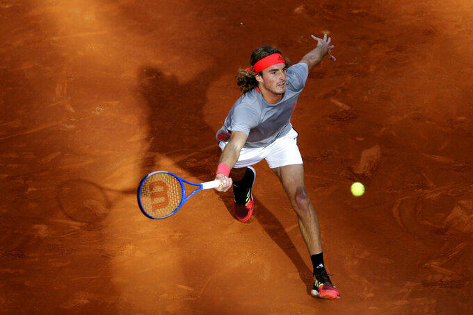 FILE - In this Sunday, May 12, 2019, file photo, Greece's Stefanos Tsitsipas plays a shot against Serbia's Novak Djokovic during the final of the Madrid Open tennis tournament in Madrid, Spain. With the sports calendar still mostly on hold because of the coronavirus pandemic, The Associated Press takes a look at some of the live sporting events that would have taken place the week of May 4-10, 2020, including the clay-court Madrid Open. (AP Photo/Bernat Armangue, File)