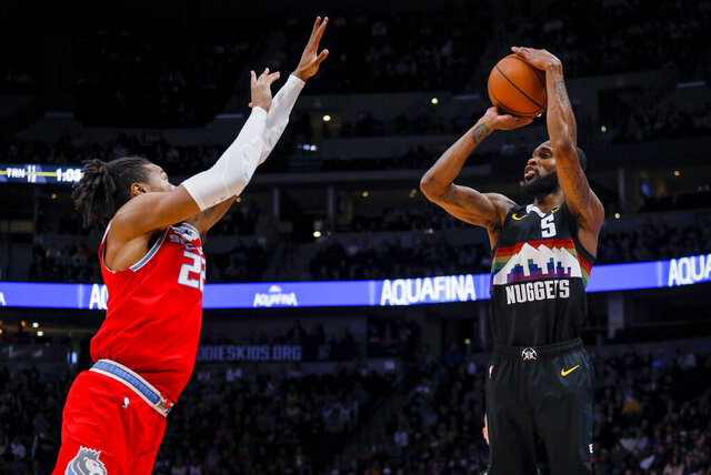 Sacramento Kings forward Richaun Holmes (22) defends Denver Nuggets guard Will Barton's, right, shot from the perimeter in the second half of an NBA basketball game Sunday, Dec. 29, 2019 in Denver. Denver won 120-115. (AP Photo/Joe Mahoney)