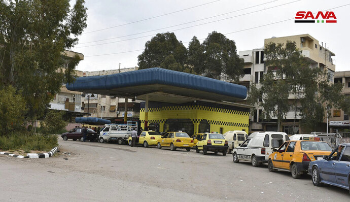 FILE - This file photo released on April 7, 2019, by the Syrian official news agency SANA, shows cars queuing to fill their tanks with fuel, at a gas station in Daraa, south Syria. As a fuel shortage crisis deepens in government-held areas of Syria, Cabinet ministers huddled in televised meetings to reassure the public they are searching for solutions. New rationing measures were rolled out, and government officials held talks with allies in Iran and Russia to explore options for the crisis aggravated by U.S. sanctions on Damascus and Tehran. (SANA via AP, File)