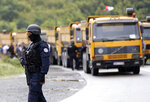 A Kosovo special police officer stands near trucks where Kosovo Serbs block a road near the northern Kosovo border crossing of Jarinje, Monday, Sept. 20, 2021. Tensions soared Monday at the border between Kosovo and Serbia as Kosovo deployed additional police to implement a rule to remove Serbian license plates from cars entering Kosovo, while Serbs protested the move. (AP Photo/Bojan Slavkovic)