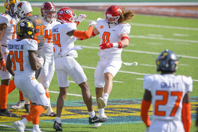American Team linebacker Grant Stuard of Houston (0) celebrates a stop during the first half of the NCAA Senior Bowl college football game in Mobile, Ala., Saturday, Jan. 30, 2021. (AP Photo/Matthew Hinton)