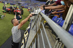 Baltimore Ravens coach John Harbaugh gives a fan his hat after practice at the NFL football team's training camp Saturday, July 31, 2021, in Baltimore. (AP Photo/Gail Burton)