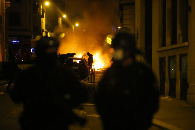 A car burns near the Champs-Elysee avenue after the Champions League soccer final match between PSG and Bayern Munich which is played in Lisbon, Portugal, Sunday Aug. 23, 2020 in Paris. Bayern Munich won 1-0. (AP Photo/Michel Euler)