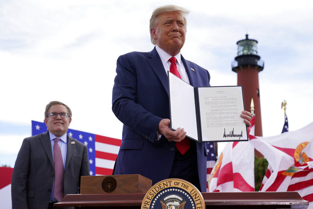 FILE - In this Sept. 8, 2020, file photo President Donald Trump holds a signed memorandum to expand the offshore drilling moratorium to Florida's Atlantic coast, Georgia and South Carolina after speaking at the Jupiter Inlet Lighthouse and Museum in Jupiter, Fla. At left is Environmental Protection Agency Administrator Andrew Wheeler. With one stroke, Trump's abrupt reversal on offshore drilling this week has loosened a political vise that was tightening around three Republicans senators running for reelection in coastal states where drilling is widely opposed. (AP Photo/Evan Vucci, File)