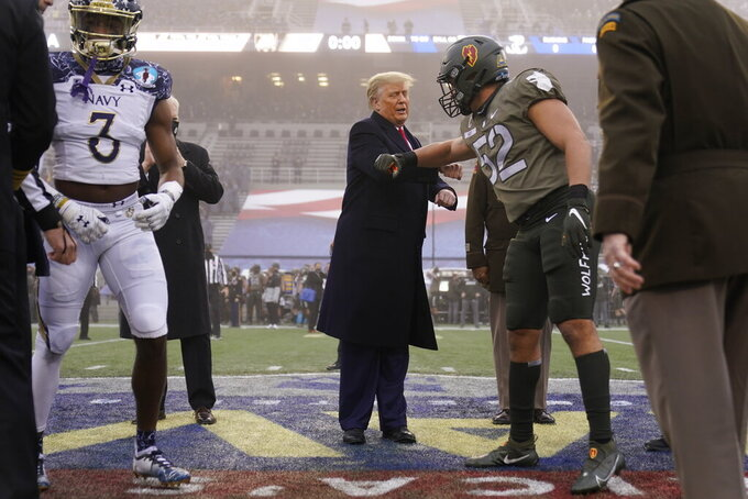 President Donald Trump elbow bumps with a player before the start of the 121st Army-Navy Football Game in Michie Stadium at the United States Military Academy, Saturday, Dec. 12, 2020, in West Point, N.Y. (AP Photo/Andrew Harnik)