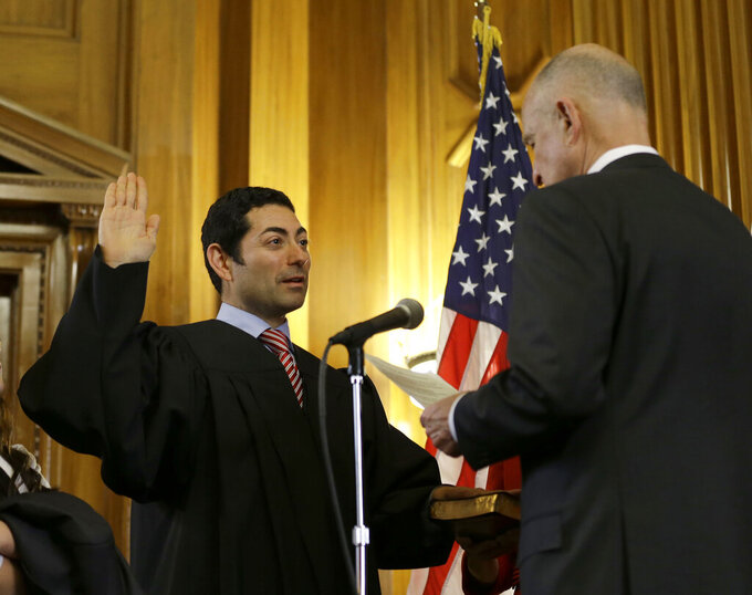 FILE - In this Jan. 5, 2015 file photo Mariano-Florentino Cuellar, left, is sworn in as an associate justice to the California Supreme Court by Gov. Jerry Brown during an inauguration ceremony in Sacramento, Calif. Cuellar announced, Thursday Sept. 16, 2021, that he will be leaving the state's high court in October 2021. (AP Photo/Rich Pedroncelli, file)