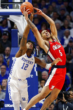 Mississippi's KJ Buffen (5) tries to pull in a pass while pressured by Kentucky's Keion Brooks Jr. (12) in the second half of an NCAA college basketball game in Lexington, Ky., Saturday, Feb. 15, 2020. Kentucky won 67-62. (AP Photo/James Crisp)