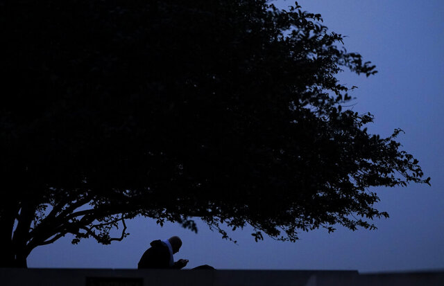 FILE - In this Sept. 19, 2020 file photo, a man looks at his phone while sitting in a park at twilight  in Kansas City, Mo. Has the whirlwind of 2020 left you with whiplash? Maybe you feel like the whole world is uncertain. While there is a lot that's beyond your control, you can take steps to put your finances on more stable ground. Start by understanding what financial stability means to you.  (AP Photo/Charlie Riedel, File)
