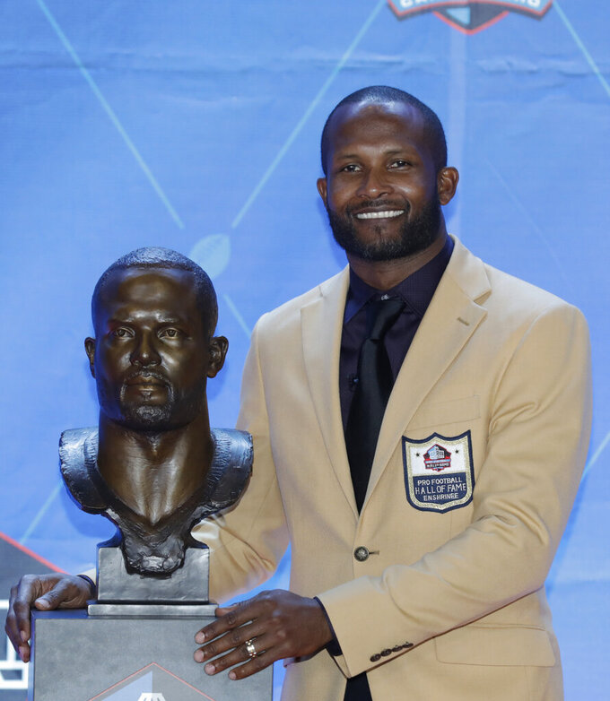 Former NFL player Champ Bailey poses with a bust of himself during the induction ceremony at the Pro Football Hall of Fame, Saturday, Aug. 3, 2019, in Canton, Ohio. (AP Photo/Ron Schwane)