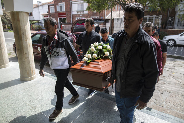 Relatives and friends of slain Astrid Conde, a former rebel of the Revolutionary Armed Forces of Colombia (FARC), carry her coffin during her funeral in Bogota, Colombia, Sunday, March 8, 2020. Conde was gunned down while walking her German shepherd in a park near her home in a rough Bogota neighborhood on March 5.  (AP Photo/Ivan Valencia)