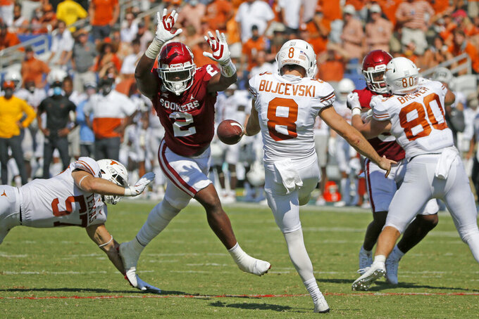 Oklahoma linebacker David Ugwoegbu (2) blocks a punt by Texas punter Ryan Bujcevski (8) during an NCAA college football game in Dallas, Saturday, Oct. 10, 2020. (AP Photo/Michael Ainsworth)