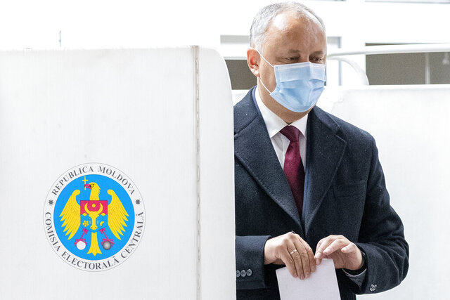 Incumbent Moldovan President Igor Dodon prepares to cast his vote in the country's presidential elections in Chisinau, Moldova, Sunday, Nov. 1, 2020. Pro-Russian incumbent Igor Dodon and former prime minister Maia Sandu, a pro-Western, anti-corruption reformer lead the race according to pre-electoral polls, both credited with a little over a third of the voting intentions which indicates an election runoff will take place.(AP Photo/Roveliu Buga)