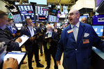 Specialist Peter Giacchi, right, calls out prices on the New York Stock Exchange trading floor before the Slack IPO, Thursday, June 20, 2019. The San Francisco company is set to start trading Thursday in what's known as a direct listing. (AP Photo/Richard Drew)