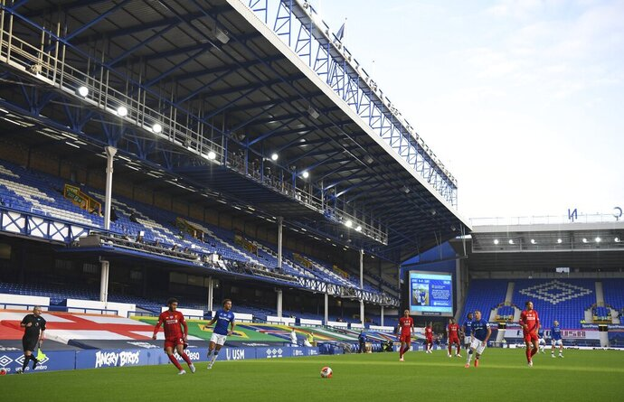 Players in action in front of the empty stands during the English Premier League soccer match between Everton and Liverpool at Goodison Park in Liverpool, England, Sunday, June 21, 2020. (AP photo/Shaun Botterill, Pool)