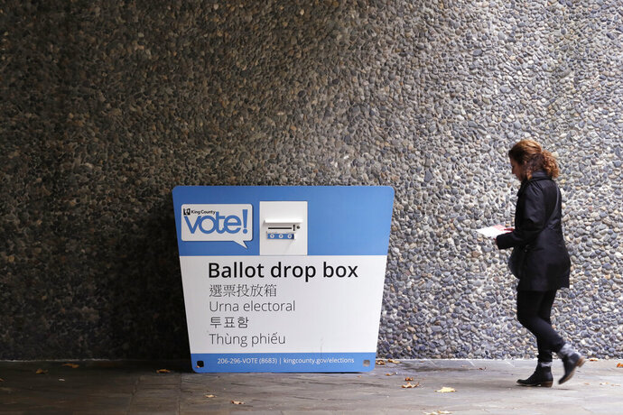 A voter heads to a ballot drop box Monday, Nov. 4, 2019, in Seattle. Voters in Washington state have a crowded ballot to fill out for this week's election, with a referendum on affirmative action and an initiative on the price of car tabs among the things they are being asked to decide. (AP Photo/Elaine Thompson)