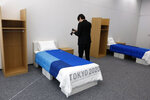 A journalist films a cardboard bed in a display room showing furniture for the Tokyo 2020 Olympic and Paralympic Villages Thursday, Jan. 9, 2020, in Tokyo. Tokyo Olympic athletes beware - particularly larger ones. The single bed frames in the Athletes Village at this year's Olympics will be made of cardboard. The single bed frames will be recycled into paper products after the games. The mattress components - the mattress are not made of cardboard - will be recycled into plastic products.. (AP Photo/Jae C. Hong)