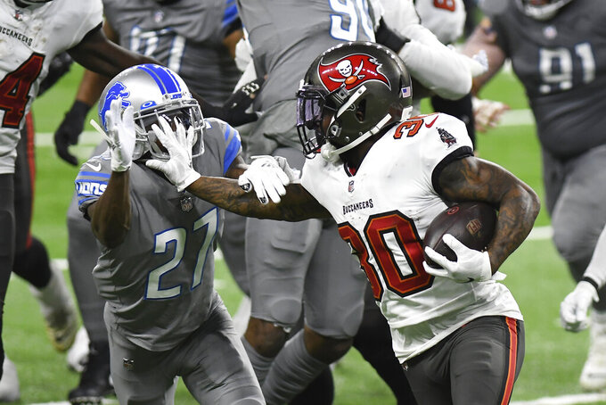 Tampa Bay Buccaneers running back Ke'Shawn Vaughn (30) stiff arms Detroit Lions cornerback Justin Coleman (27) during the second half of an NFL football game, Saturday, Dec. 26, 2020, in Detroit. (AP Photo/Lon Horwedel)