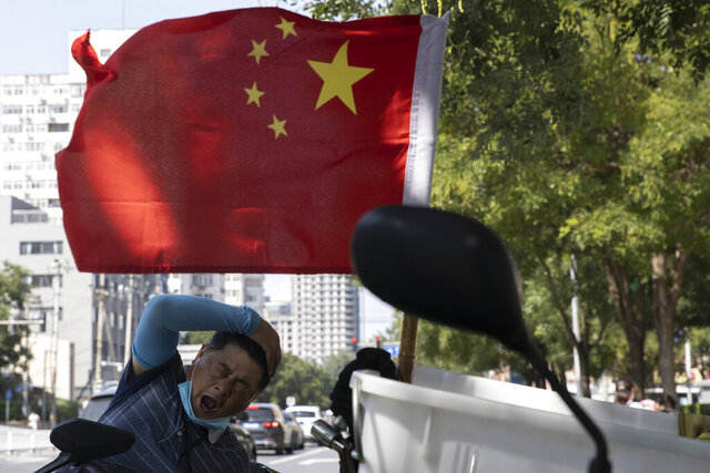 A delivery man yawns near a national flag in Beijing on Wednesday, Sept. 2, 2020. China's Ministry of Commerce on Saturday, Sept. 19 2020 issued regulations for its