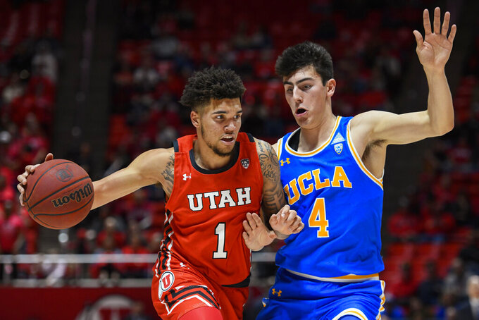 Utah forward Timmy Allen (1) drives as UCLA guard Jaime Jaquez Jr. (4) defends during the second half of an NCAA college basketball game Thursday, Feb. 20, 2020, in Salt Lake City. (AP Photo/Alex Goodlett)