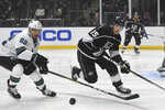 San Jose Sharks right wing Kevin Labanc, left, and Los Angeles Kings defenseman Ben Hutton chase the puck during the first period of an NHL hockey game, Monday, Nov. 25, 2019, in Los Angeles. (AP Photo/Michael Owen Baker)