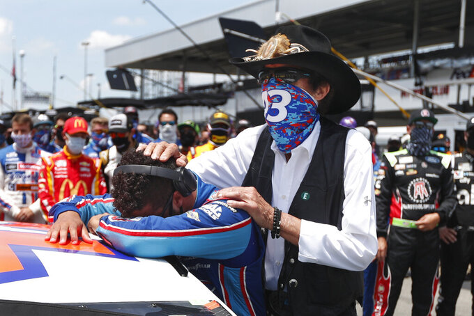 NASCAR driver Bubba Wallace is consoled by team owner Richard Petty, right, prior to the start of the NASCAR Cup Series at the Talladega Superspeedway in Talladega, Ala., Monday, June 22, 2020. In an extraordinary act of solidarity with Wallace, NASCAR's only Black driver, dozens of drivers pushed his car to the front of the field before Monday's race. (AP Photo/John Bazemore)