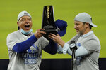 Los Angeles Dodgers manager Dave Roberts, left, and President of Baseball Operations Andrew Friedman celebrate with the trophy after winning Game 7 of a baseball National League Championship Series against the Atlanta Braves Sunday, Oct. 18, 2020, in Arlington, Texas. (AP Photo/Eric Gay)