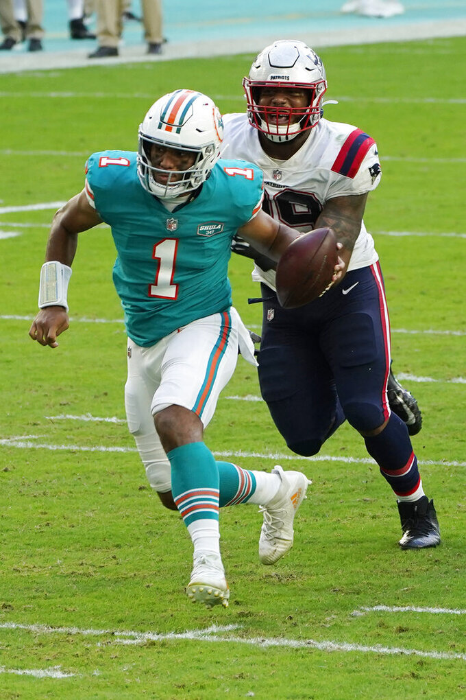 Miami Dolphins quarterback Tua Tagovailoa (1) runs for a touchdown ahead of New England Patriots defensive tackle Byron Cowart (99), during the second half of an NFL football game, Sunday, Dec. 20, 2020, in Miami Gardens, Fla. (AP Photo/Chris O'Meara)