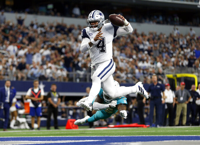 FILE- In this Sunday, Sept. 22, 2019, file photo, Dallas Cowboys quarterback Dak Prescott (4) gets past Miami Dolphins defensive back Walt Aikens (35) and into the end zone for a touchdown in the second half of an NFL football game in Arlington, Texas. With the Cowboys at 3-0, their fans are beginning to see America's Team as a team of destiny. (AP Photo/Ron Jenkins, File)
