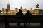 "FILE - In this file photo dated Saturday, Dec. 14, 2019, a couple takes photos of Houses of Parliament in London. With a hefty government majority, expectations for the coming year are high and Prime Minister Boris Johnson has pledged to ""work my socks off"" to unite the divided country. (AP Photo/Thanassis Stavrakis, FILE)"