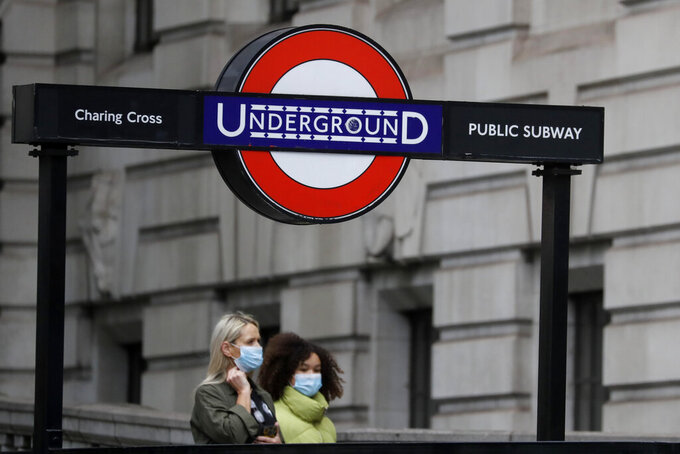 Pedestrians wear masks as they walk near Charing Cross Station in London, Friday, June 5, 2020. It will become compulsory to wear face coverings whilst using public transport in England from Monday June 15. (AP Photo/Kirsty Wigglesworth)