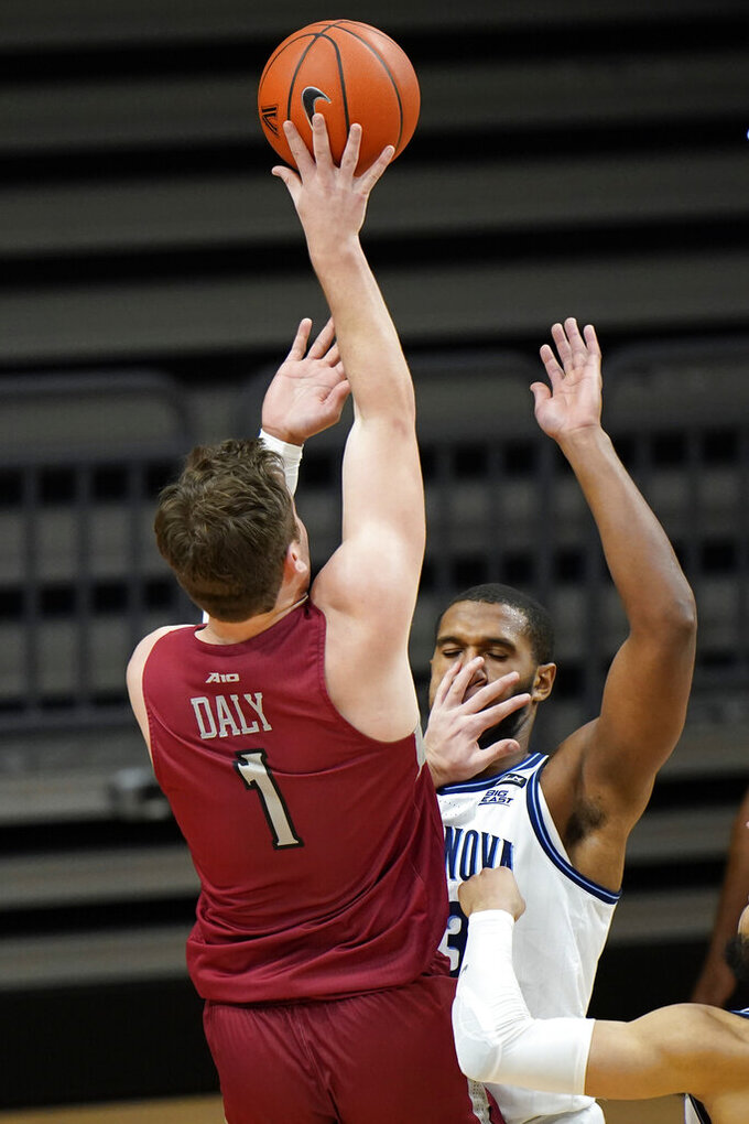 Saint Joseph's Ryan Daly, left, goes up for a shot against Villanova's Eric Dixon during the second half of an NCAA college basketball game, Saturday, Dec. 19, 2020, in Villanova, Pa. (AP Photo/Matt Slocum)