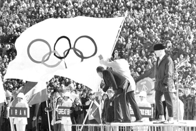 FILE - In this  Feb. 3, 1972, file photo, the white five-ringer Olympic flag, which has been in the custody of Genoble since the winter games in 1968, is handed over by French skier Ingrid Lafforgue, with due ceremony in Sapporo. The city of Sapporo is the first to officially bid for the 2030 Winter Olympics and becomes the early favorite after the Japanese Olympic Committee approved its candidate file late Wednesday, Jan. 29, 2020. Sapporo was host to the 1972 Winter Olympics and could face competition from Salt Lake City in the United States, which is also being mentioned as a possible bidder, along with Barcelona and a bid tied to the Pyrenees. At right is Avery Brundage, the president of the IOC. (AP Photo, File)