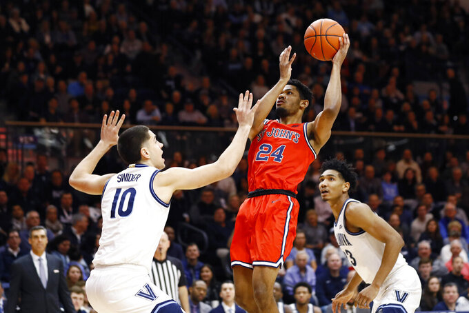 St. John's Nick Rutherford (24) goes up for a shot between Villanova's Cole Swider (10) and Jermaine Samuels (23) during the first half of an NCAA college basketball game, Wednesday, Feb. 26, 2020, in Villanova, Pa. (AP Photo/Matt Slocum)