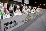 Jury members of the Bocuse d'Or gastronomy contest are pictured during a visit of French President at the International Catering, Hotel and Food Trade Fair (SIRHA) in Lyon, central France, Monday Sept. 27, 2021. (Ludovic Marin, Pool Photo via AP)
