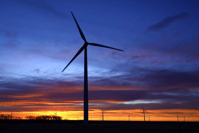 """FILE - In this Jan. 13, 2021, file photo, wind turbines are silhouetted against the sky at dawn near Spearville, Kan. The $1 trillion bipartisan infrastructure package unveiled by the Senate includes more than $150 billion to boost clean energy and promote """"climate resilience"""" by making schools, ports and other structures better able to withstand extreme weather events such as storms and wildfires.  But the bill, headed for a Senate vote this week, falls far short of President Joe Biden's pledge to  transform the nation's heavily fossil-fuel powered economy into a clean-burning one and stop climate-damaging emissions from U.S. power plants by 2035.  Notably, the deal omits mention of a Clean Electricity Standard, a key element of Biden's climate plan that would require the electric grid to replace fossil fuels with renewable sources such as solar, wind and hydropower. (AP Photo/Charlie Riedel, File)"""
