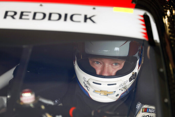 Tyler Reddick sits in his car during practice for a NASCAR Xfinity Series auto race, Saturday, June 15, 2019, at Iowa Speedway in Newton, Iowa. (AP Photo/Charlie Neibergall)