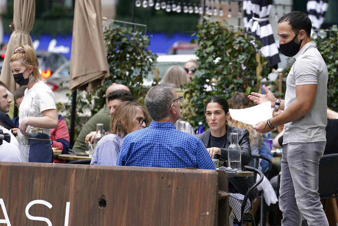 Patrons at a sidewalk cafe are seated without masks, Sunday, May 2, 2021, in Boston. In Massachusetts as of Friday, April 30, 2021, masks are only required outside in public when it's not possible to maintain a distance of approximately 6 feet from others, or when required for other reasons, including at outdoor events.(AP Photo/Steven Senne)