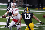 Wisconsin quarterback Graham Mertz (5) passes while getting pressured by Iowa defensive end Joe Evans (13) during the first half of an NCAA college football game, Saturday, Dec. 12, 2020, in Iowa City, Iowa. (AP Photo/Charlie Neibergall)