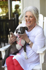 In this April 26, 2019 photo, Paula Deen holds an animal shelter dog up for adoption during an appearance at her recently opened Paula Deen's Family Kitchen in Destin, Fla. The restaurant, which opened in March 2019, and another recently opened Paula Deen's Family Kitchen restaurant in nearby Panama City Beach, Fla., were abruptly closed Monday, Nov. 11, 2019.  (Devon Ravine/Northwest Florida Daily News via AP)