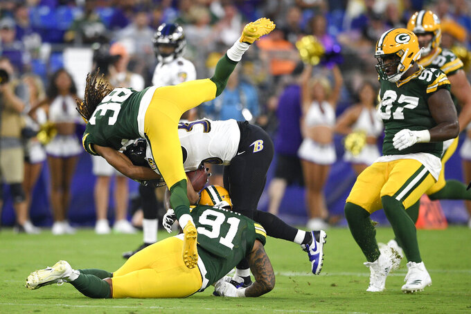 Baltimore Ravens running back Kenneth Dixon, center, is brought down by Green Bay Packers cornerback Tramon Williams (38) and outside linebacker Preston Smith (91) during the first half of a NFL football preseason game, Thursday, Aug. 15, 2019, in Baltimore. (AP Photo/Nick Wass)